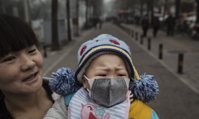 A Chinese girl wears a mask as she is held by her mother outside a local hospital during a day of heavy smog in Beijing on Dec. 8, 2015.   (Kevin Frayer/Getty Images)