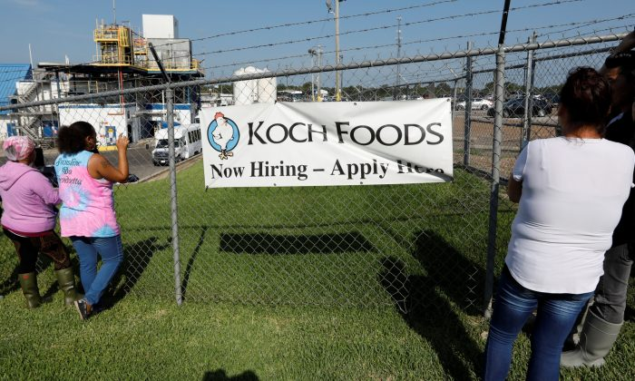 Onlookers watch as immigration officials carry out an operation at a Koch Foods meat processing plant in Morton, Miss., on Aug. 7, 2019. (Rogelio V. Solis/AP Photo)