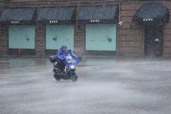 A man rides an electric scooter in the rainstorm as typhoon Lekima approaches in Shanghai