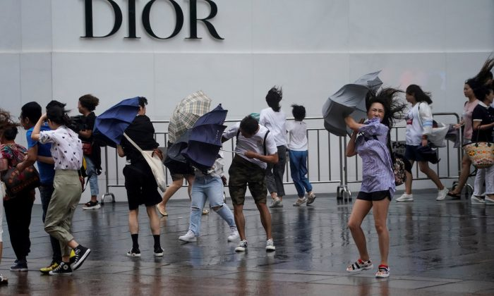People walk in the rainstorm as typhoon Lekima approaches in Shanghai, China on Aug. 10, 2019. (REUTERS/Aly Song)