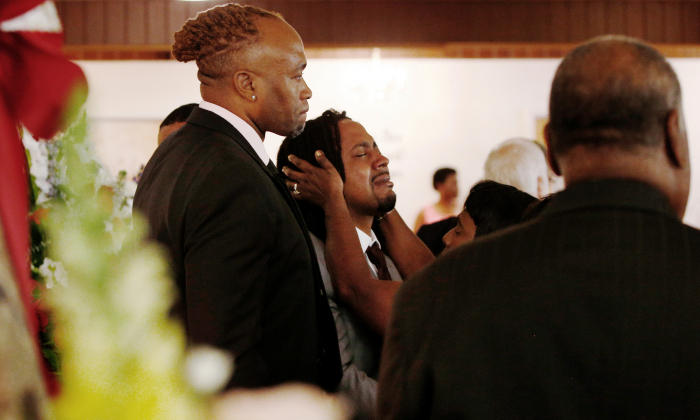 A relative attempts to console Dion Green (C), before the funeral for his father, Derrick Fudge, on Aug. 10, 2019, at a church in Springfield, Ohio. (Angie Wang/AP)