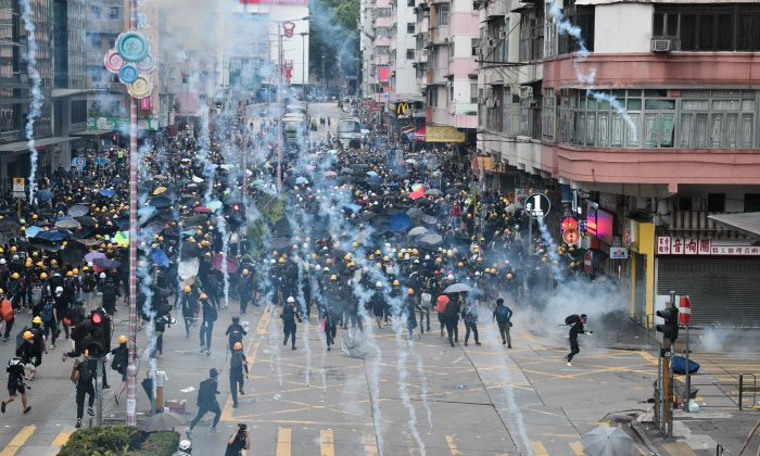 Pro-democracy protesters throw back tear gas fired by the police during a demonstration against the controversial extradition bill in Sham Shui Po district in Hong Kong on Aug. 11, 2019. (Anthony Wallace/AFP/Getty Images)