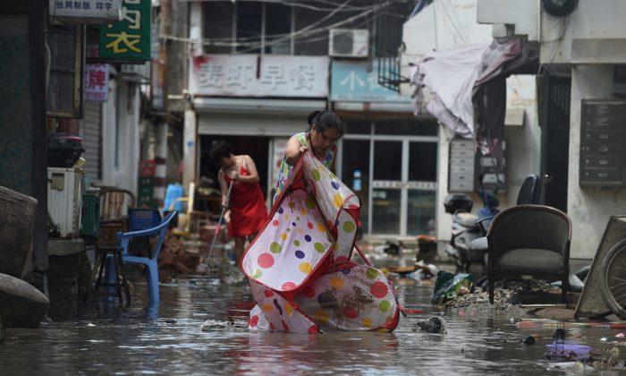People clean a flooded street after typhoon Lekima hit Linhai City of Taizhou, Zhejiang Province, China on Aug. 11, 2019.  (Reuters)