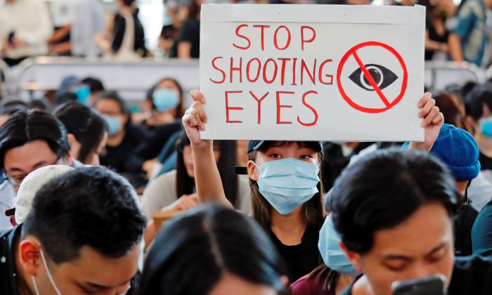 Anti-extradition bill protesters attend a mass demonstration after a woman was shot in the eye during a protest at Hong Kong International Airport, in Hong Kong, China August 12, 2019. REUTERS/Tyrone Siu