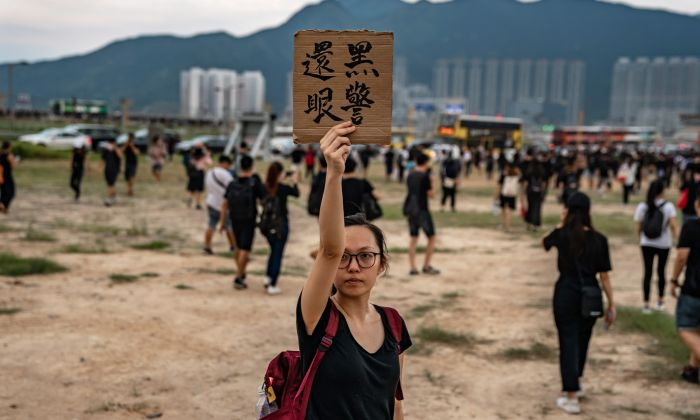 A protester holds up a placard which translates as 'policeman pay the eye back' outside the Hong Kong International Airport as protesters retreat during a demonstration in Hong Kong on Aug. 12, 2019. (Anthony Kwan/Getty Images)