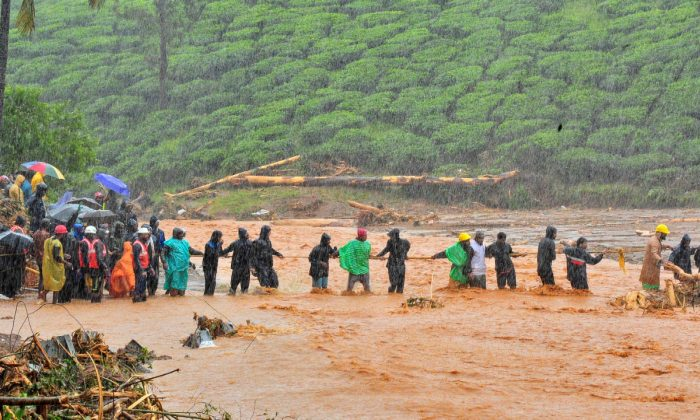 Rescuers help people to cross a flooded area after a landslide caused by torrential monsoon rains in Meppadi in Wayanad district in the southern Indian state of Kerala, India on Aug. 9, 2019. (Stringer/Reuters)