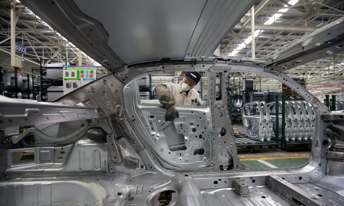 An employee installs car doors at a production line of Dongfeng Peugeot Citroen Automobile factory in Wuhan, Hubei Province, China on Feb. 13, 2014. (Darley Shen/Reuters)