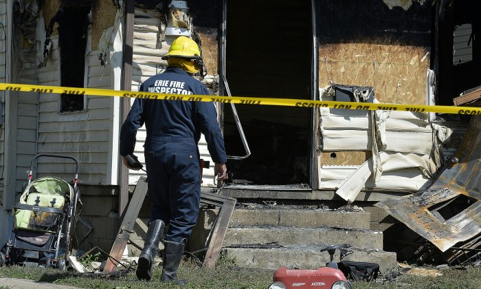 Erie Bureau of Fire Inspector Mark Polanski helps investigate a fatal fire at 1248 West 11th St. in Erie, Pa., on Aug. 11, 2019. (Greg Wohlford/Erie Times-News via AP)