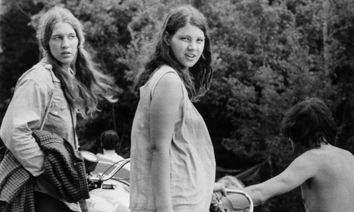 August 1969:  A pregnant woman and her friend wait as a motorcycle is unhitched from a car, as they prepare to leave Max Yasgur's Bethil farm and the Woodstock music festival.  (Photo by Three Lions/Getty Images)