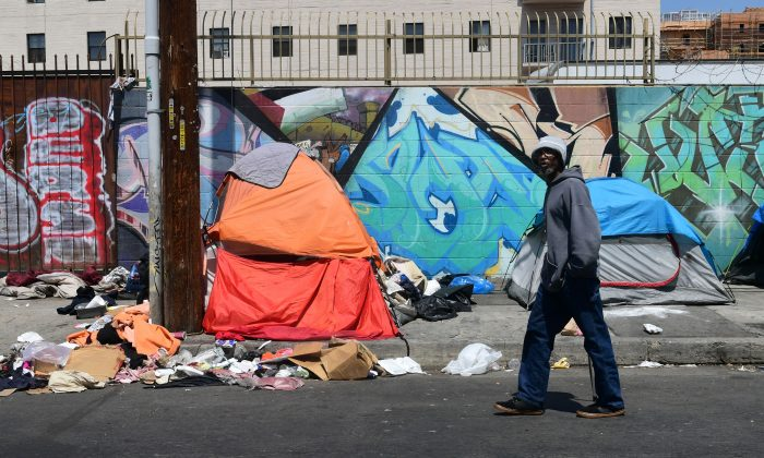 A pedestrian walks past tents and trash on a sidewalk in downtown Los Angeles on May 30, 2019. (Frederic J. Brown/AFP/Getty Images)