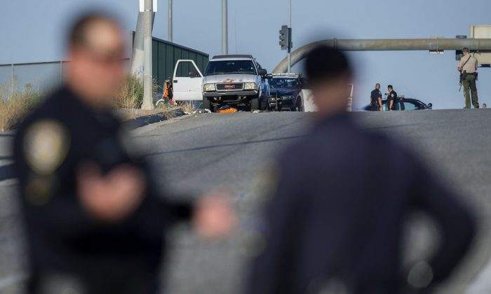 Authorities work the scene where a shootout near a freeway killed a California Highway Patrol officer and wounded two others before the gunman was fatally shot, in Riverside, Calif., on Aug. 12, 2019. (Terry Pierson/The Orange County Register via AP)