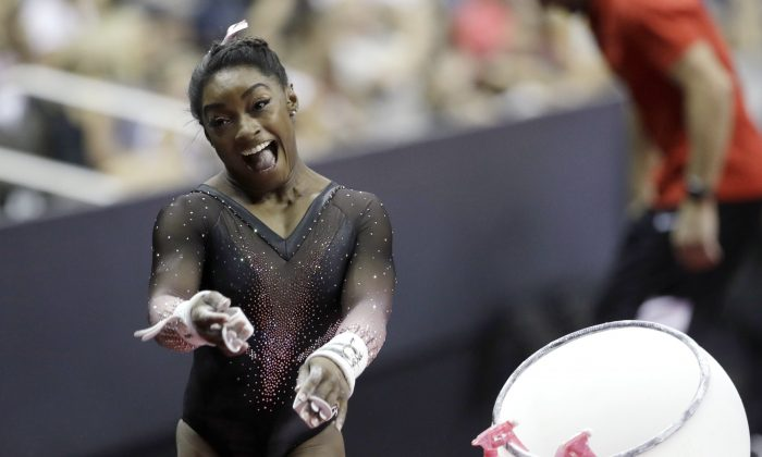 Simone Biles celebrates after competing in the uneven bars to win the all around senior women's competition at the 2019 U.S. Gymnastics Championships on Aug. 11, 2019, in Kansas City, Mo. (Charlie Riedel/AP Photo)