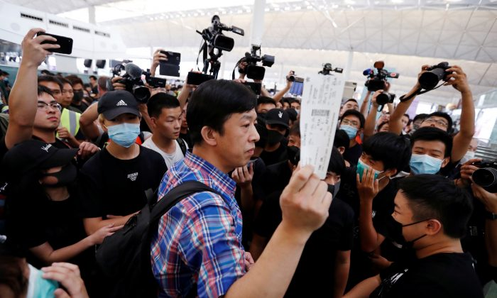 A passenger walks past anti-government protesters as he tries to enter the security gate during a demonstration at Hong Kong Airport, China on Aug. 13, 2019. (Issei Kato/Reuters)