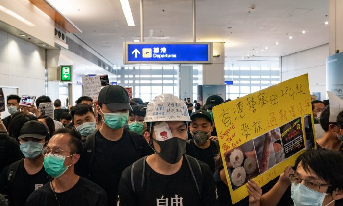 Protesters hold placards as they block the departure gate of the Hong Kong International Airport Terminal 2 during a demonstration in Hong Kong, on Aug. 13, 2019. (Anthony Kwan/Getty Images)