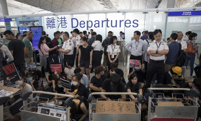 Airport security personnel stand guard as travelers walk past protesters holding a sit-in rally at the departure gate of the Hong Kong International Airport in Hong Kong, China on Aug. 13, 2019. (Vincent Thian/AP)