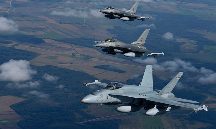 A CF-18 Hornet from the Canadian Air Task Force Lithuania flies beside two Portuguese F-16 Fighting Falcons over Lithuania for the NATO Baltic Air Policing Block 36 mission during Operation Reassurance on Sept. 15, 2014. (Canadian Armed Forces)