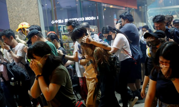 Anti-extradition bill protesters react after the police fired tear gas to disperse the demonstration at Sham Shui Po, in Hong Kong on Aug. 14, 2019. (Reuters/Tyrone Siu)
