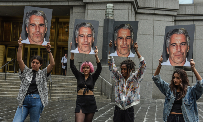"A protest group called ""Hot Mess"" hold up signs of Jeffrey Epstein in front of the dederal courthouse in New York City on July 8, 2019. (Stephanie Keith/Getty Images)"
