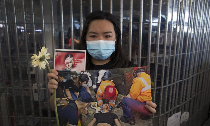 A woman holds a flower and posters showing people injured by police as protesters stage a sit-in rally at he Hong Kong International Airport in Hong Kong, on Aug. 13, 2019. (AP Photo/Vincent Thian)