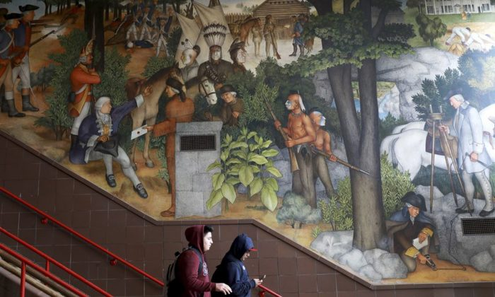 A pair of students walk past a historic mural that includes slaves and a dead Native American at George Washington High School in San Francisco. The San Fransisco school board unanimously voted on June 25, 2019, to destroy a controversial mural displayed in a public high school. (Yalonda M. James/San Francisco Chronicle via AP)