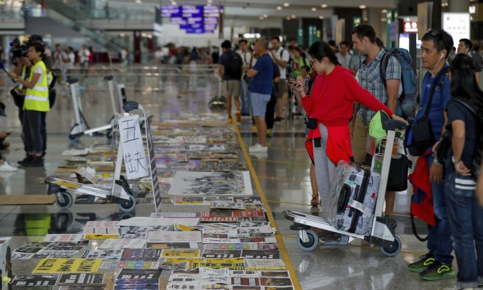 Traveller look at placards and posters placed by protesters at the airport in Hong Kong, China on Aug. 14, 2019. (Vincent Thian/AP)