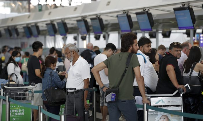 Travelers wait to check in for their flights at the airport in Hong Kong on Aug. 14, 2019. (Vincent Thian/AP Photo)