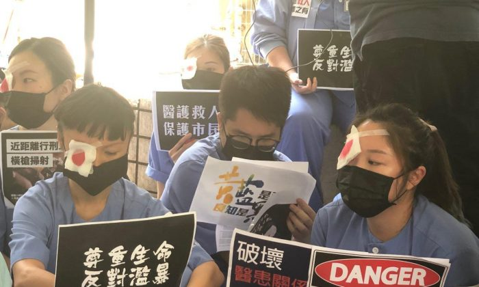 Hundreds of hospital workers from Ruttonjee and Tang Shiu Kin hospitals in Hong Kong staged another sit-in outside Ruttonjee Hospital on Aug. 14 in support of the protesters and condemned the brutality of the police.  (Ye Yifan/Epoch Times)