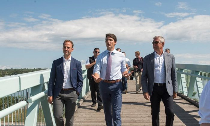 Prime Minister Justin Trudeau, center, walks across a pedestrian bridge next to the St. John River in downtown Fredericton with Member of Parliament for Fredericton Matt DeCourcey, left, and Mayor of Fredericton Mike O'Brien walk in Fredericton, New Brunswick on August 15, 2019. Trudeau was in Fredericton to discuss federal funding for flood mitigation. (Stephen MacGillivray/The Canadian Press)