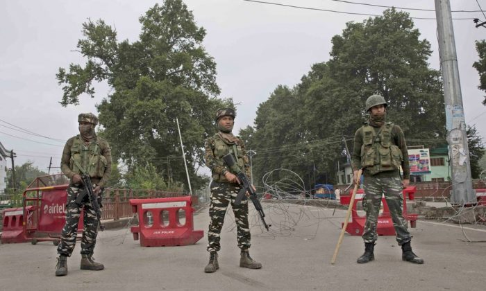 Indian paramilitary soldiers stand guard near a temporary check post on the road leading towards Independence Day parade venue during lockdown in Srinagar, Indian controlled Kashmir, on Aug. 15, 2019. (Dar Yasin/AP Photo/)