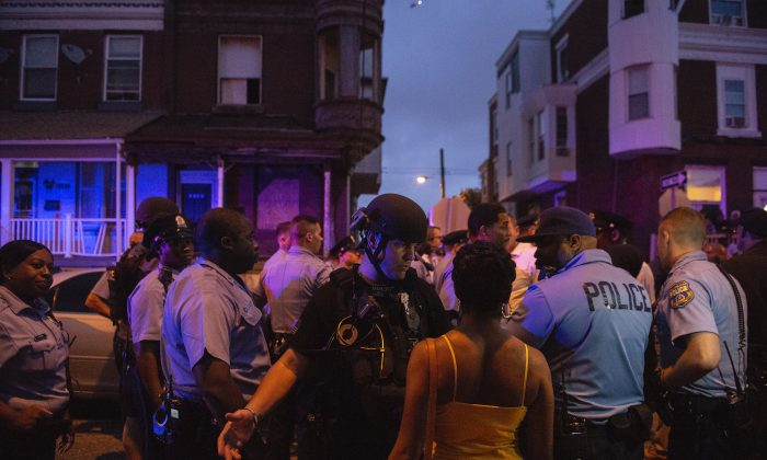 Police officers gather for crowd control during a shooting investigation in Philadelphia on Wednesday, Aug. 14, 2019. (Joe Lamberti/Camden Courier-Post via AP)