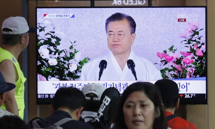 "People watch a TV screen showing a live broadcast of South Korean President Moon Jae-in's speech during a ceremony to celebrate the Korean Liberation Day, marking the 74th anniversary of Korea's liberation from the Japanese colonial rule, at the Seoul Railway Station in Seoul, South Korea, on Aug. 15, 2019. The signs read: ""Korean Liberation Day."" (AP Photo/Ahn Young-joon)"