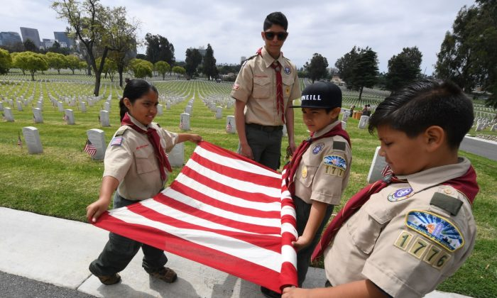 Boy Scouts prepare a U.S. flag besides the graves of war veterans during the annual 'Flag Placement ceremony' to honor the fallen for Memorial Day at the Los Angeles National Cemetery, Calif., on May 25, 2019. (Mark Ralston/AFP/Getty Images)