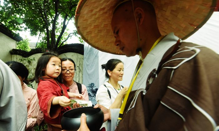A monk receives donation from a girl during a traditional mendicants' walk in Hangzhou in China's eastern Zhejiang Province on May 22, 2018. Monks walked from Faxi Temple to Lingyin Temple as they received donations from residents for charity, to mark the birthday of Shakyamuni, founder of Buddhism. (AFP/Getty Images)