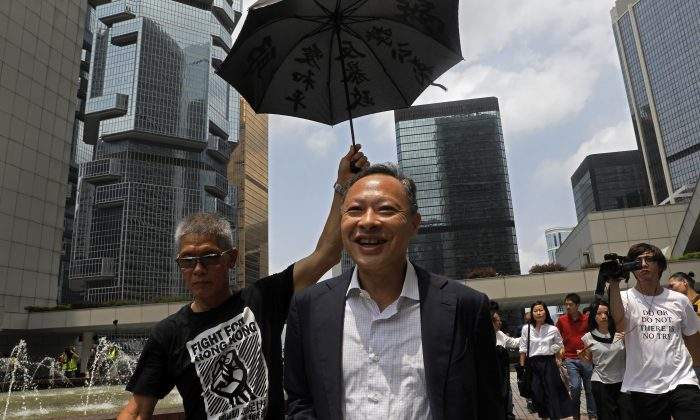 Occupy Central leader Benny Tai, center, is  accompanied by a supporter who raises an umbrella as he leaves High court in Hong Kong on Aug.15, 2019. Tai, a top opposition leader imprisoned on public disorder charges was released on bail. (Vincent Yu/AP)