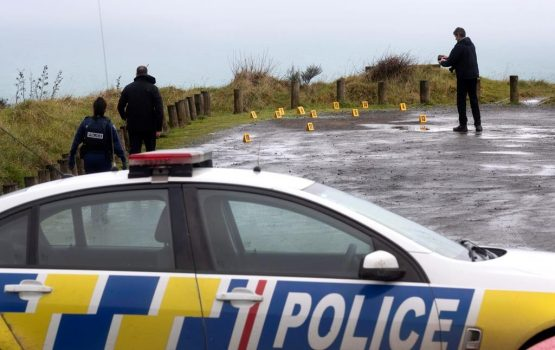 Police collect and photograph evidence in the carpark of the Te Toto Gorge lookout on Whaanga Rd, south of Raglan, New Zealand, Aug. 16, 2019. (AP, Alan Gibson/New Zealand Herald/The Canadian Press)