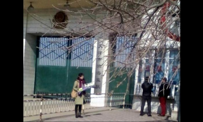 Ge Xiulan stands outside Binhai Prison holding flowers for her incarcerated husband on his birthday in 2018. Prison authorities didn't allow her to visit him that day. (Minghui.org)