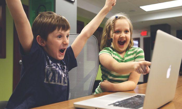 Boy and girl looking at laptop. (Pixabay)