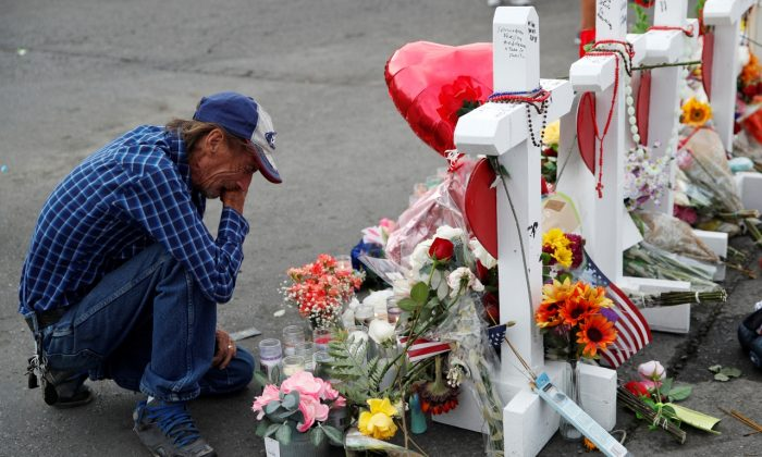 Antonio Basco cries beside a cross at a makeshift memorial near the scene of a mass shooting at a shopping complex in El Paso, Texas on Aug. 6, 2019. (John Locher/AP Photo)