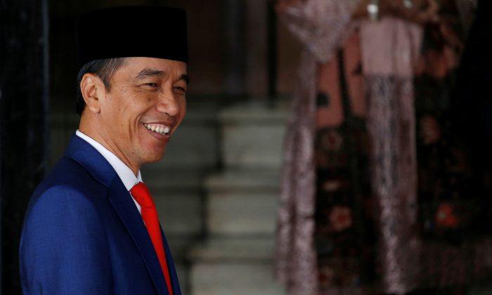 Indonesian President Joko Widodo smiles at reporters as he arrives before delivering a speech ahead of Independence Day, at the parliament building in Jakarta, Indonesia, on Aug. 16, 2019. (Willy Kurniawan/Reuters)