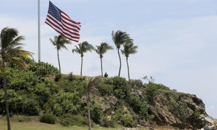 A man stands near a U.S. flag at half staff on Little St. James Island, in the U. S. Virgin Islands, a property owned by Jeffrey Epstein on Aug. 14, 2019. (Gabriel Lopez Albarran/AP Photo)