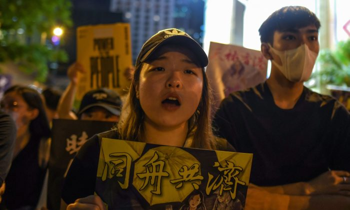 Pro-democracy protesters hold signs as they attend a rally in Hong Kong on Aug. 16, 2019. (Manan Vatsyayana/AFP/Getty Images)