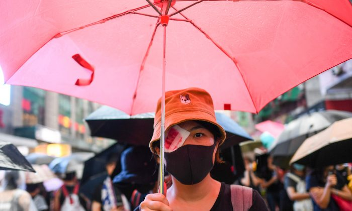 A protester wearing an eye patch, after a woman suffered an eye injury which demonstrators blamed on a bean-bag round fired by police, walks along a street during a rally in Hong Kong on Aug. 18, 2019. (Manan Vatsyayana/AFP/Getty Images)