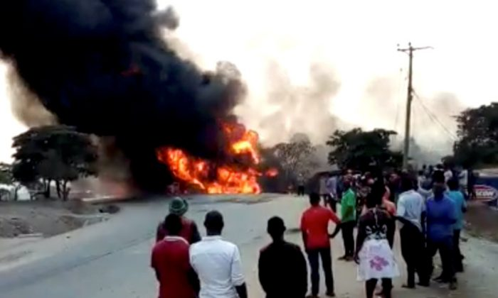 People look towards a fire following a fuel truck collision in Rubirizi, Uganda on Aug. 18, 2019 in this still image taken from social media video. (Nayebare Ediger via Reuters)