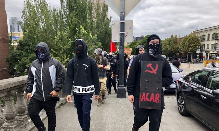 Antifa members cross Burnside Bridge across the Willamette River from the west side of the city to the east side in search of conservative ralliers in Portland, Oregon on Aug. 17, 2019. (AP Photo/Gillian Flaccus)