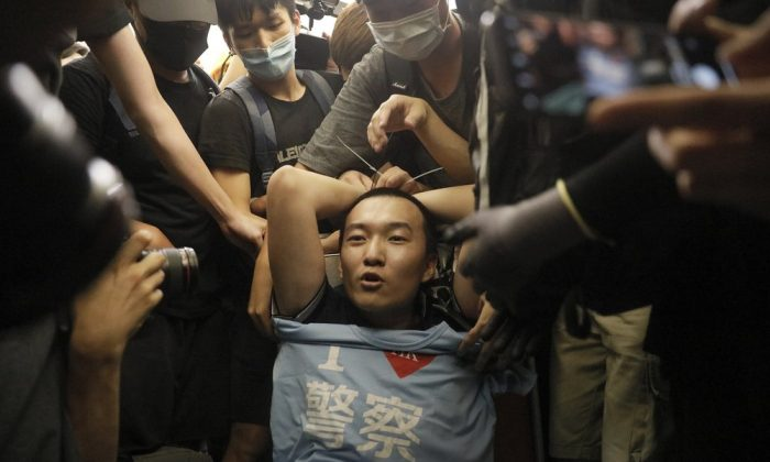 "Protesters surround a man carrying a t-shirt baring the words ""I love police"" who protesters claimed was a police officer from mainland China, during a demonstration at the Airport in Hong Kong, on Aug. 13, 2019. (AP Photo/Vincent Yu)"