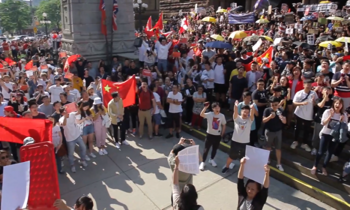 A pro-Beijing group carrying the five-starred red flag blocks Hong Kong supporters from marching at a rally in downtown Toronto on Aug. 17, 2019. (Arek Rusek/NTD Television)