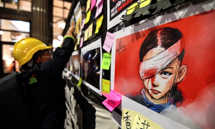 Sticky-notes carrying messages of support for Hong Kong's pro-democracy protesters and an image of a woman who suffered an eye injury, which demonstrators have blamed on a bean-bag round fired by police, are displayed during a demonstration at Martin Place in Sydney on Aug. 16, 2019. (Saeed Khan/AFP/Getty Images)