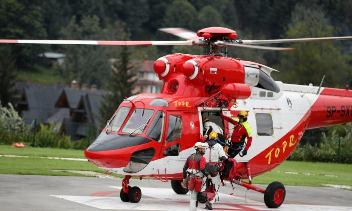 Mountain rescue team (TOPR) members board a helicopter in Zakopane, Poland August 18, 2019, to join the search operation for two cave climbers trapped in the Tatra mountains. (Agencja Gazeta/Marek Podmokly via REUTERS)