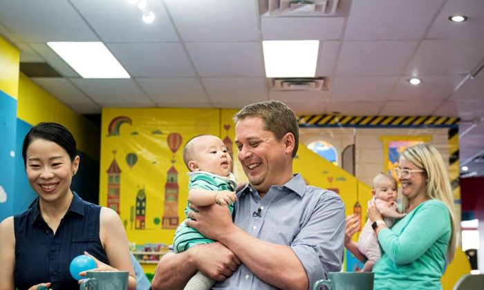 Federal Conservative leader Andrew Sheer holds 4-month old Antonio Wang while caregiver Anna Yang watches at a child care facility where he gave an announcement, on August 20, 2019. (Christopher Katsarov/The Canadian Press)