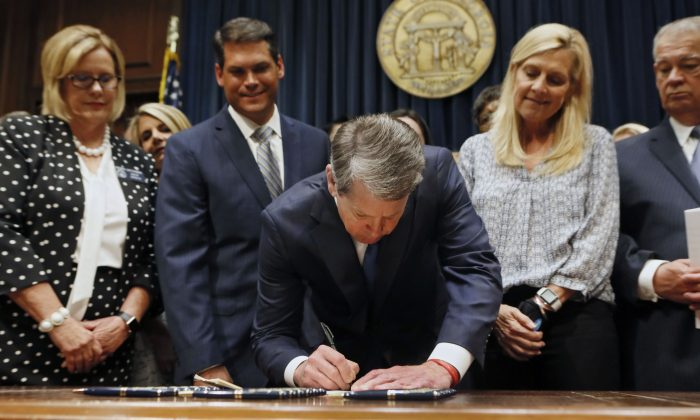 Georgia's Gov. Brian Kemp, center, signs legislation banning abortions once a fetal heartbeat can be detected in Atlanta on May 7, 2019. Bob Andres/Atlanta Journal-Constitution via AP, File